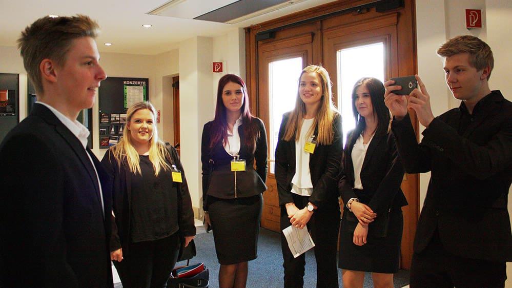 Des apprentis en 2ème année posent des questions à leurs collègues sur scènes lors de l'assemblée du Conseil d'administration.